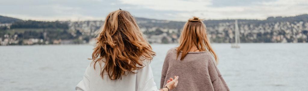 Zwei junge Frauen, die von hinten fotografiert wurden und in Richtung Hafengewässer schauen