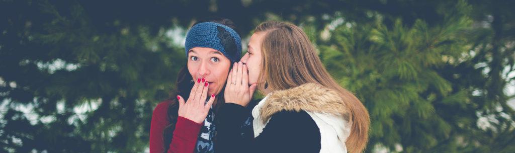 Eine junge Frau schaut gespeilt erschrocken und legt die Hand vor den Mund, während eine andere ihr etwas ins Ohr flüstert